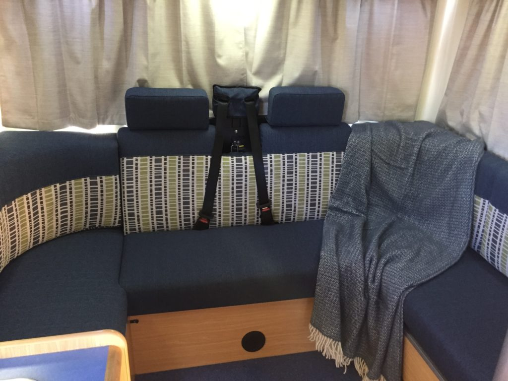 Motorhome seating area trimmed in navy with grey, white and green patterned accent