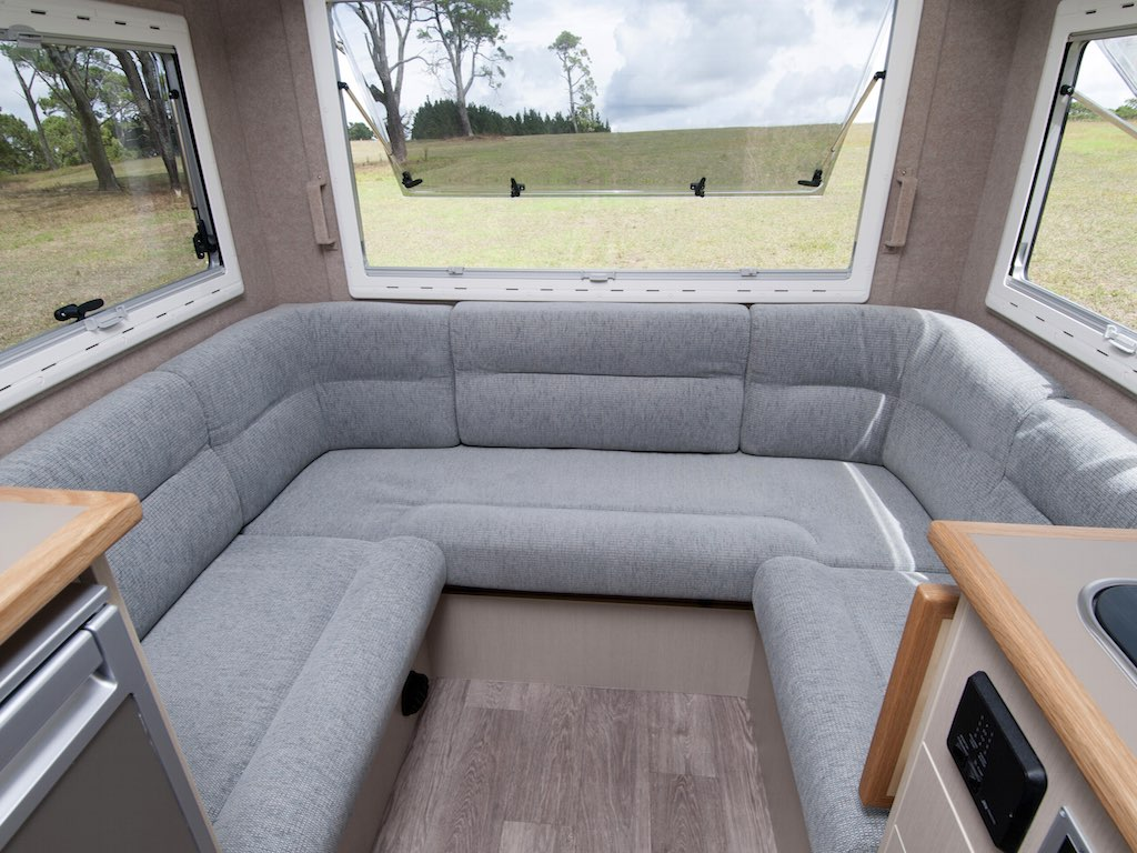Motorhome seating in grey trim. Grass in background through window
