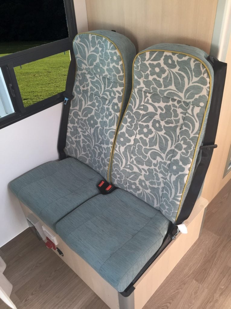 Motorhome second row seating in light blue and floral fabric with 3 point seat belts