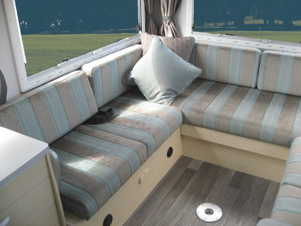 Motorhome seating in grey and blue stripe. Grey throw cushion sits in corner. Grass in background through window