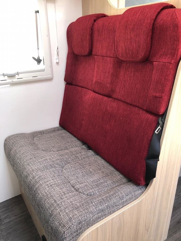 Passenger seating in motorhome trimmed in beige seat with red seat back