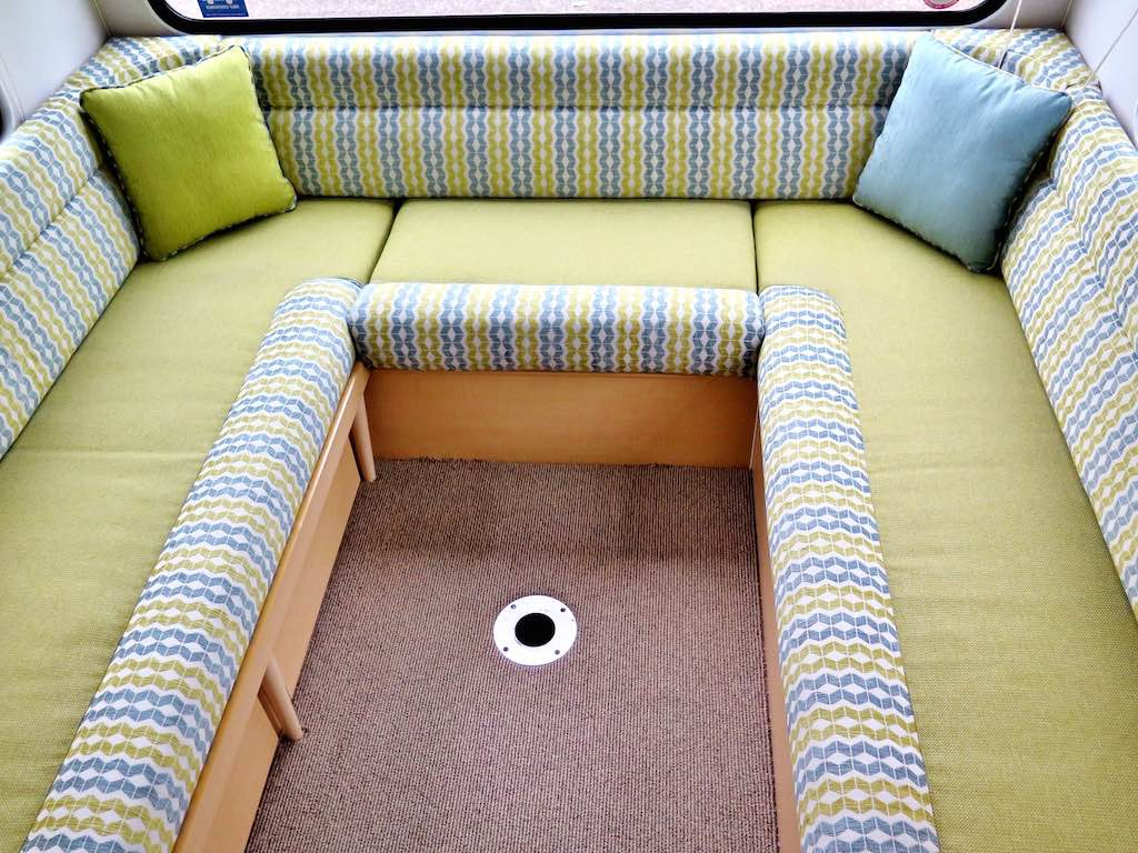 Motorhome interior with lime coloured base trim accented by a white, lime and blue geometric pattern. Throw pillows sit in each corner.