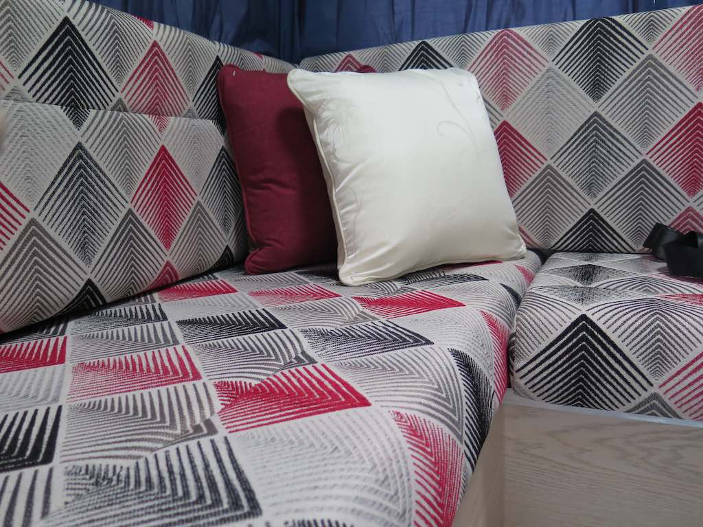 Cushions trimmed with a fabric in a black, white and red geometric pattern