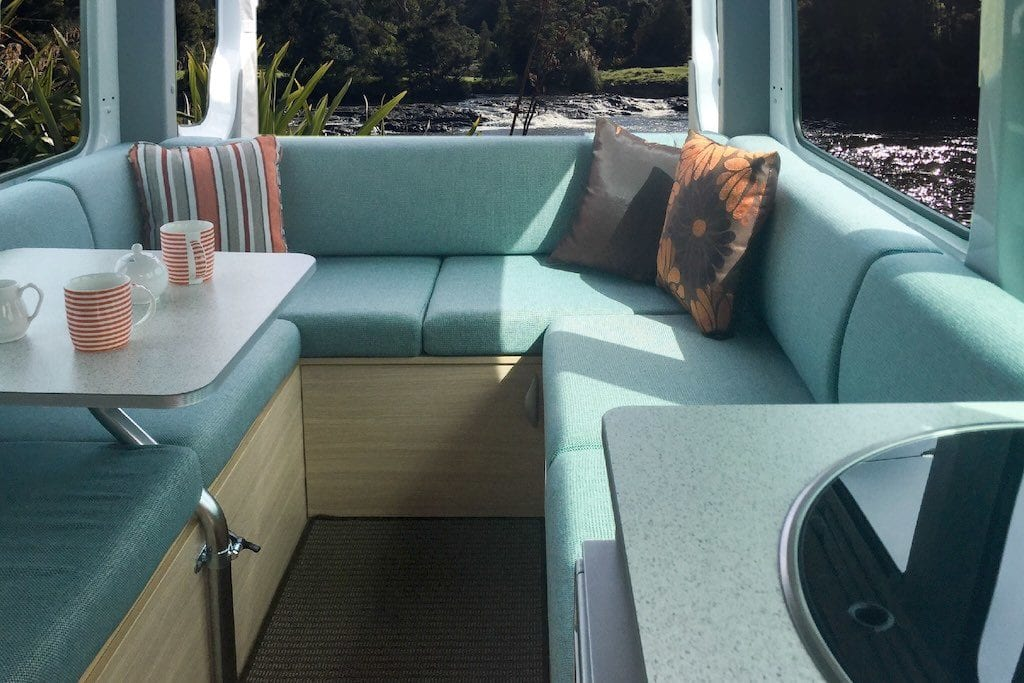 Motorhome lounge with cushions in a soft green shade. Throw cushions sit in each corner of the lounge. Table with dinnerware sits to the left hand side. Scenery can be seen through the windows.