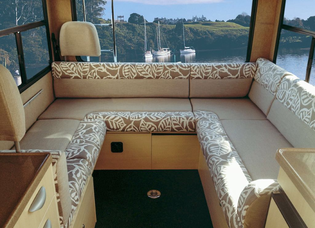 Motorhome lounge cushions in beige with leaf patterned edges. Water with boats are in the background through the rear window