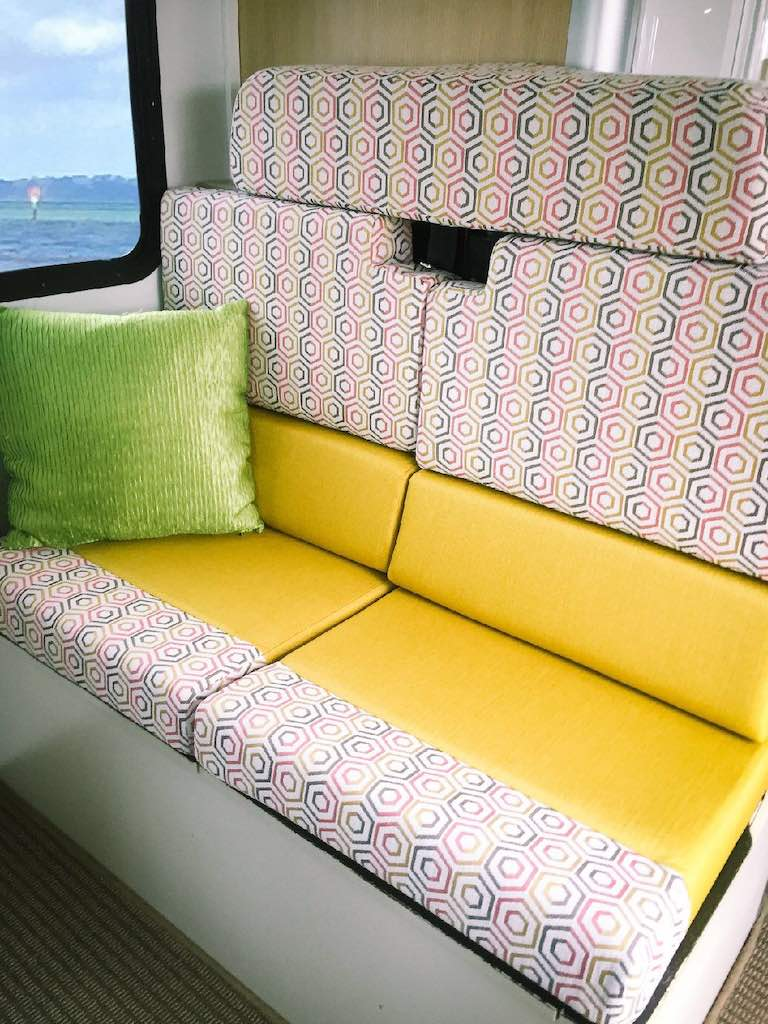 Motorhome dinette seating upholstered in yellow with a pink, grey, white geometric accent trim. A green throw cushion sits against the wall.