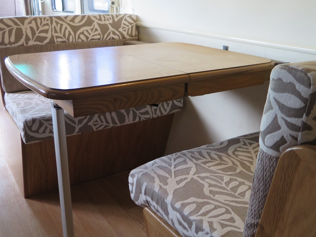 Front and Rear facing dinette with table in the middle. Upholstered in beige and white leaf pattered fabric.